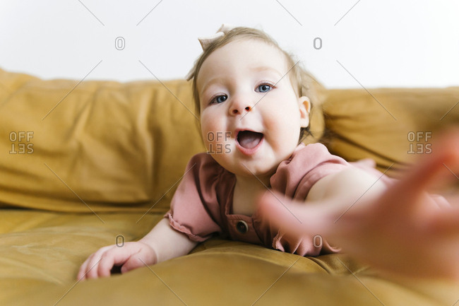 Baby girl reaching for camera on sofa