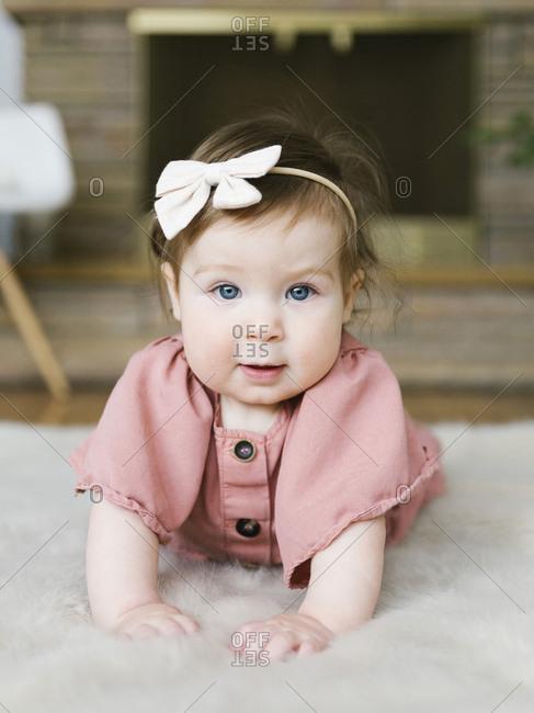 Baby girl wearing bow hair band lying on rug