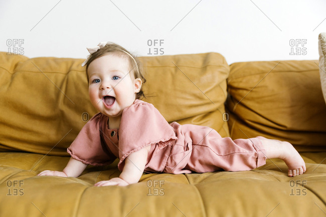 Baby girl wearing pink outfit on sofa