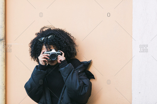 Young woman taking photograph against orange wall