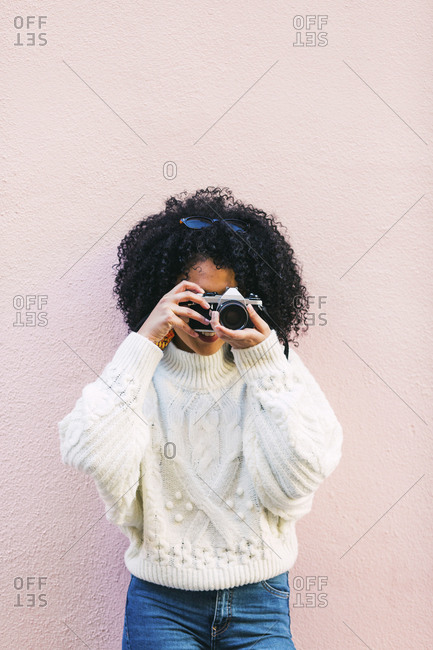 Young woman taking photograph against pink wall