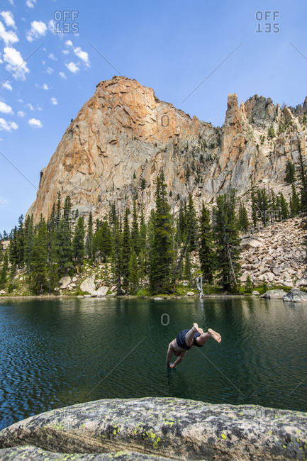Man diving into lake by mountain in Stanley, Idaho, USA
