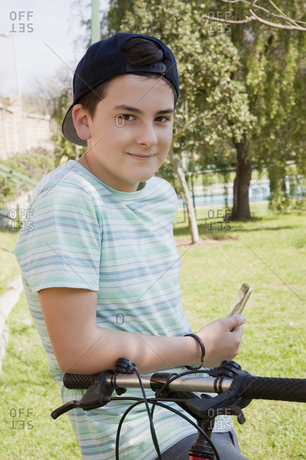 Teenage boy holding smart phone with his bicycle