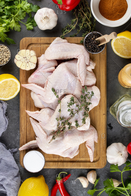 Raw chicken on cutting board surrounded by ingredients
