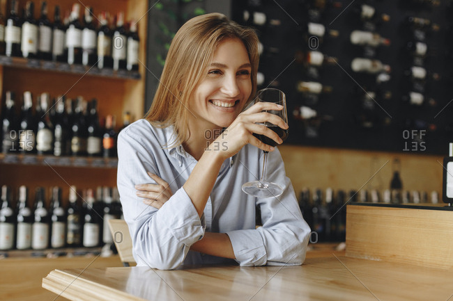 Smiling young woman holding glass of red wine