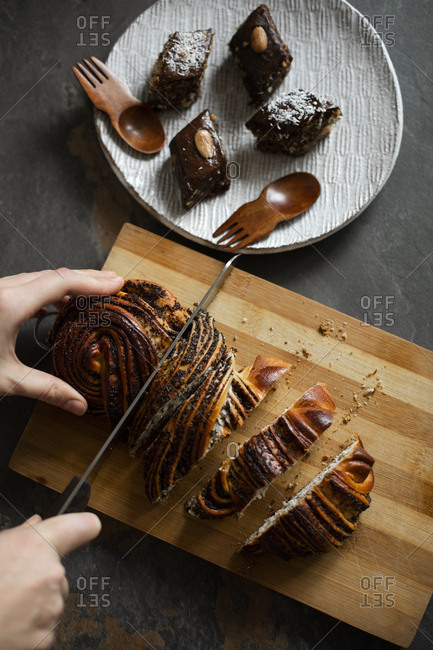 Woman cutting pastry by brownies