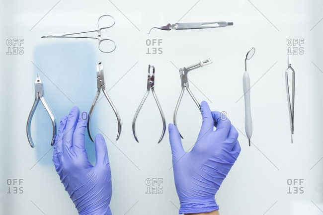 Hands of dental assistant wearing rubber gloves with dental equipment