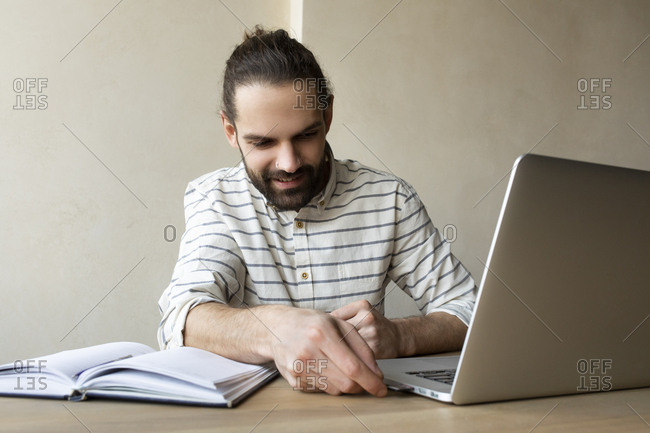 Young businessman putting USB stick into laptop