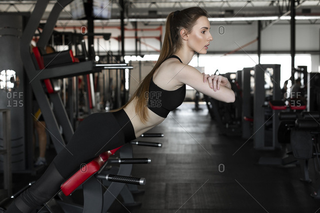 Young woman doing reverse sit-ups in gym