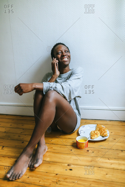 Woman sitting on floor talking on mobile phone while having breakfast