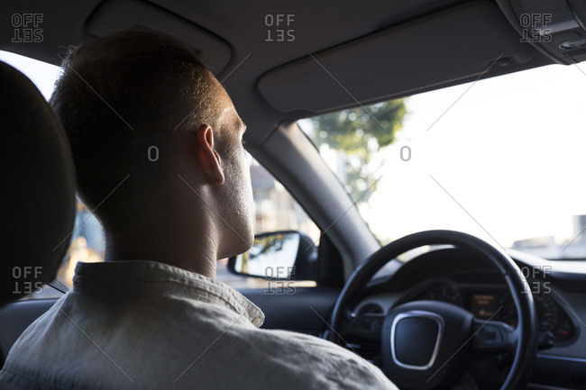 Rear view of young man driving car at sunset