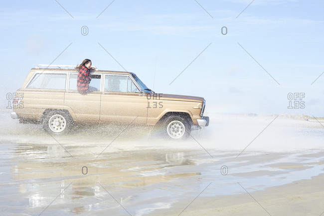 Germany- St Peter-Ording- girl leaning out of window of off-road vehicle driving through water on the beach