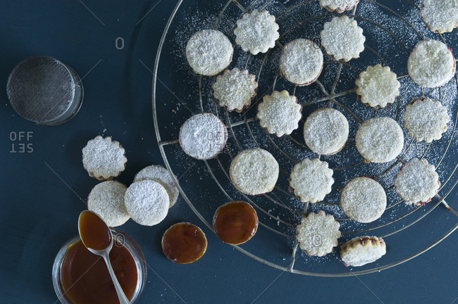Christmas Cookies Spitzbuben on a baking grid- jam in a jar- Rosehip Jam- icing sugar