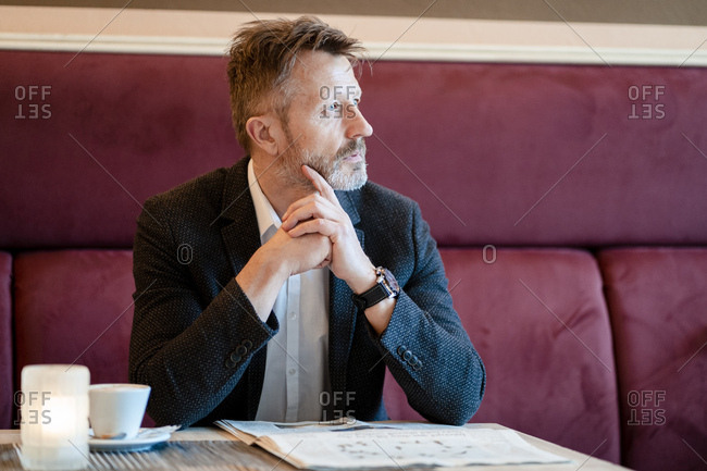 Pensive mature businessman with newspaper in a coffee shop