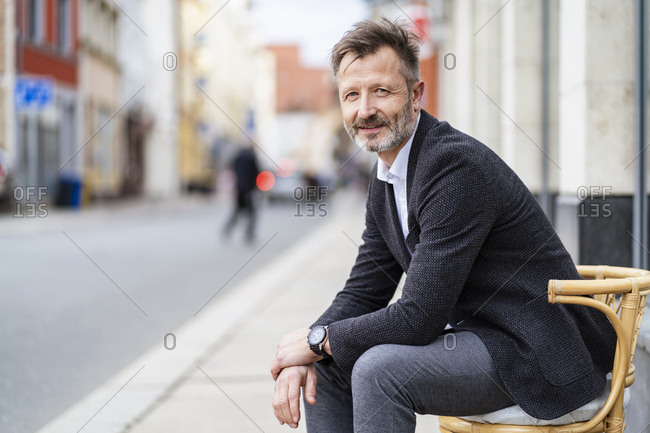 Portrait of smiling mature businessman sitting on a chair in the city