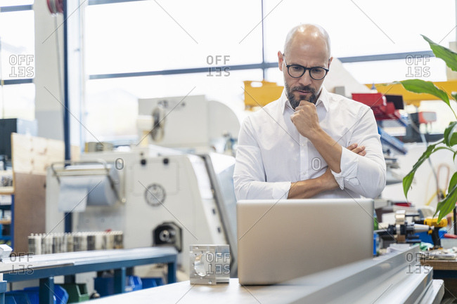 Focused businessman using laptop in factory