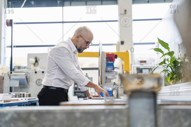 Focused businessman examining work piece in factory