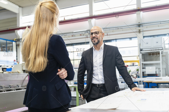 Smiling businessman and businesswoman with plan on table in factory