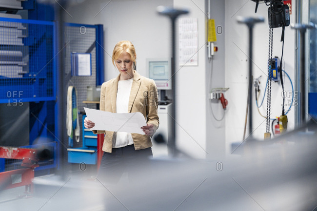 Businesswoman looking at plan in factory