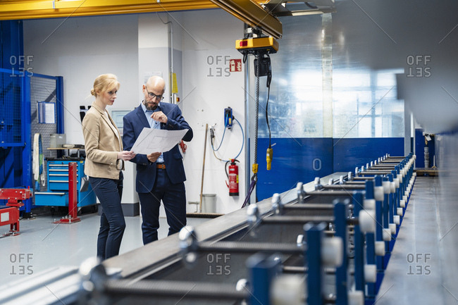 Businessman and businesswoman looking at plan in factory