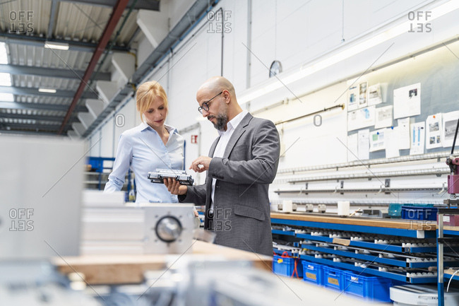 Businessman and businesswoman examining work piece in factory