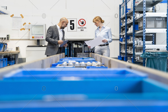 Businessman and businesswoman with tablet and plan in factory