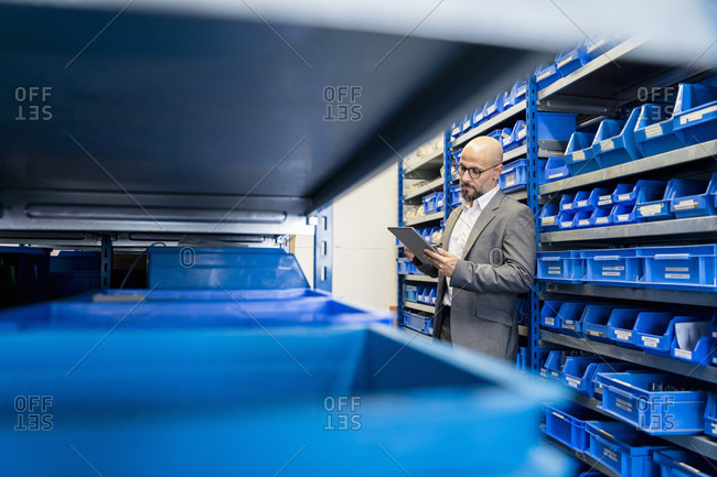 Businessman with tablet in factory storehouse