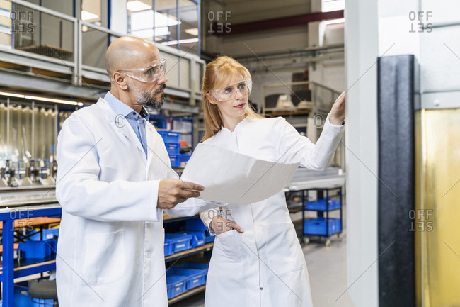Two technicians wearing lab coats and safety glasses examining machine