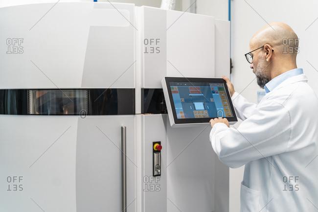 Technician wearing lab coat operating 3d printer