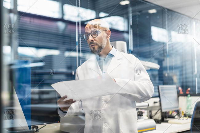 Man wearing lab coat holding plan