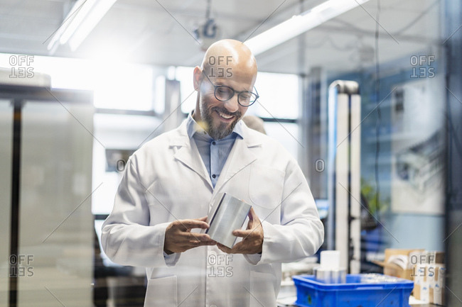 Smiling technician wearing lab coat examining work piece