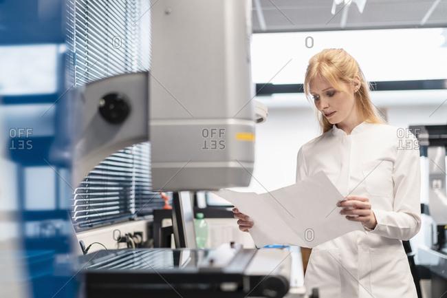 Woman wearing lab coat looking at plan