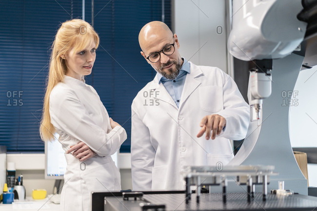 Two technicians wearing lab coats standing at machine