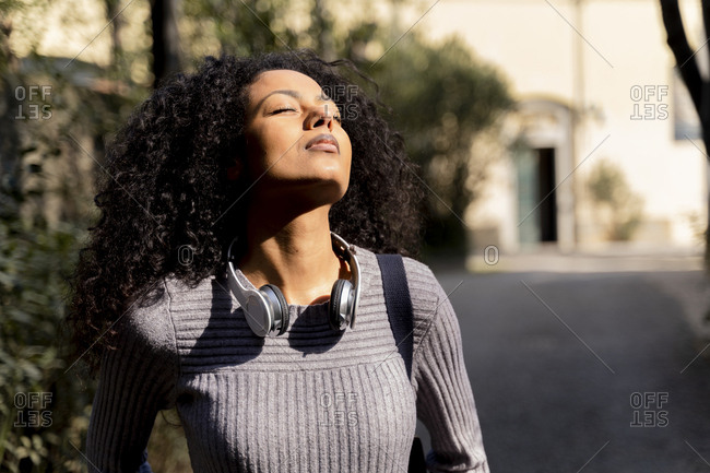 Portrait of a woman with headphones- enjoying the sun with closed eyes