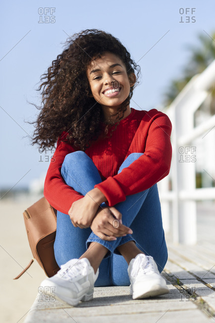 Portrait of happy young woman sitting on beach promenade