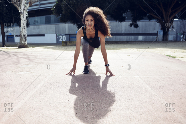 Sporty young woman on tartan track starting