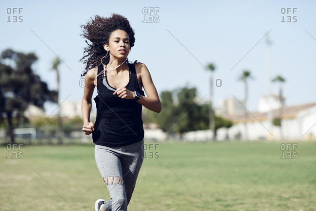 Sporty young woman with earphones running