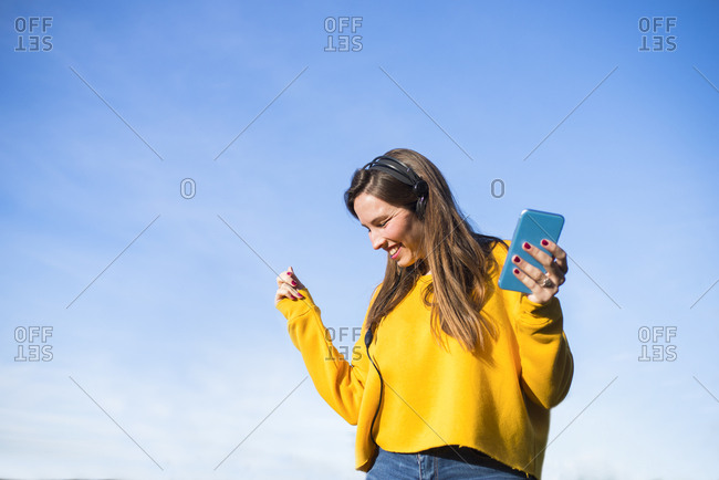 Happy young woman with cell phone listening to music with headphones