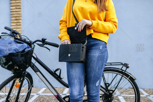 Close-up of woman with bicycle looking in handbag