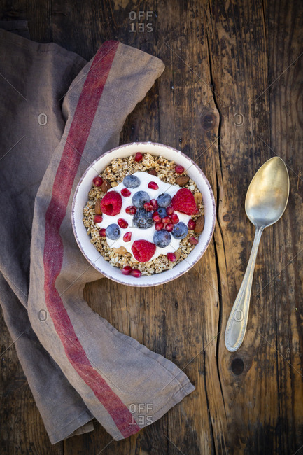 Bowl of muesli with Greek yogurt- popped quinoa- raspberries- blueberries and pomegranate seeds- from above