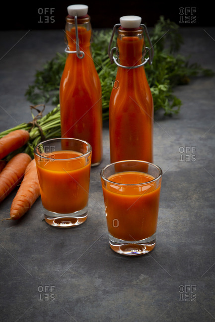 Carrot juice in bottles and glasses- bunch of carrots