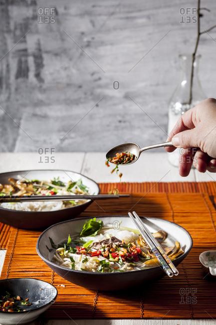 Woman's hand garnishing Vietnamese rice noodle soup