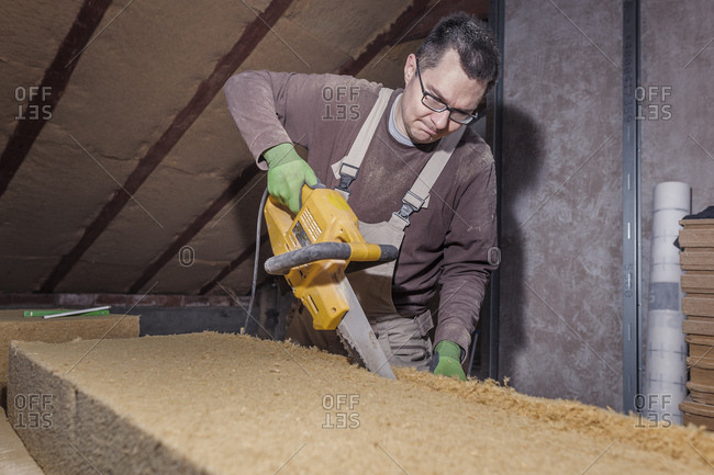 Roof insulation- worker placing wood fiber insulation at the roof