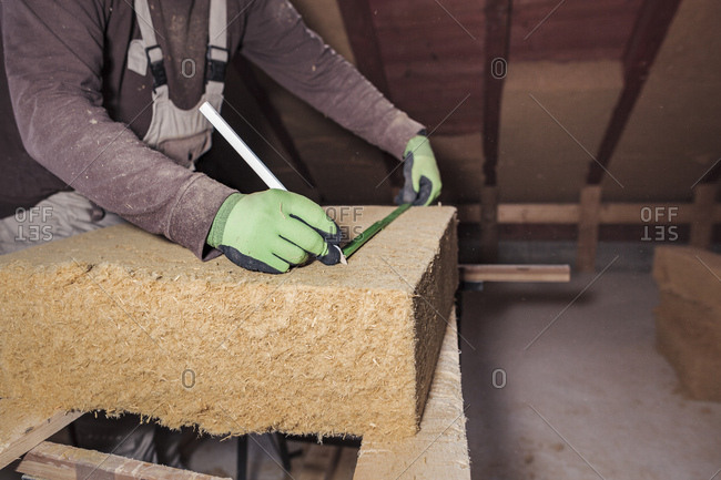 Roof insulation- worker measuring wood fiber insulation