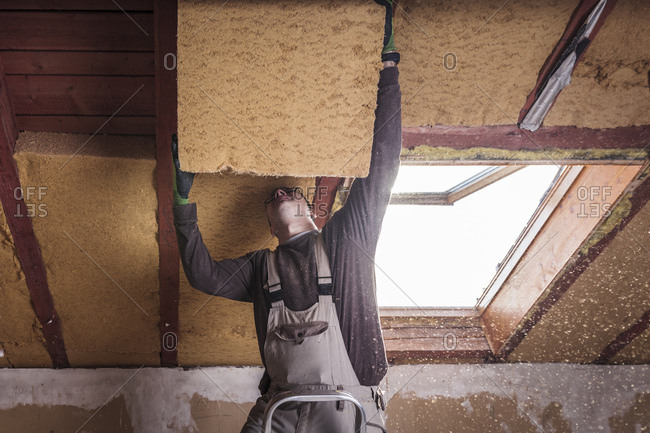 Roof insulation- worker filling pitched roof with wood fiber insulation