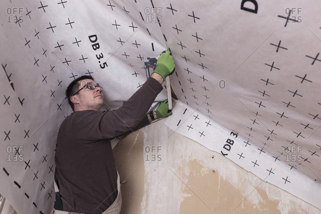 Roof insulation- worker fixing sarking membrane