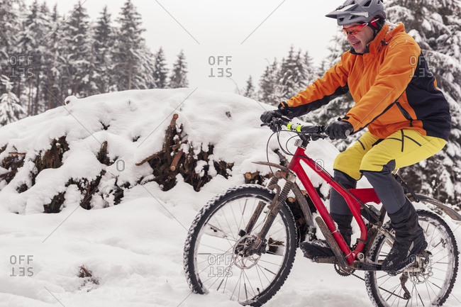 Man riding mountain bike on path in winter forest