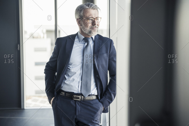 Smiling mature manager looking out of window in office