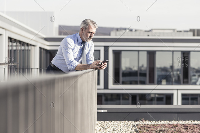 Mature businessman using cell phone on roof terrace