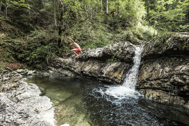 Germany- Upper Bavaria- Bavarian Prealps- lake Walchen- young man is jumping into a plunge pool